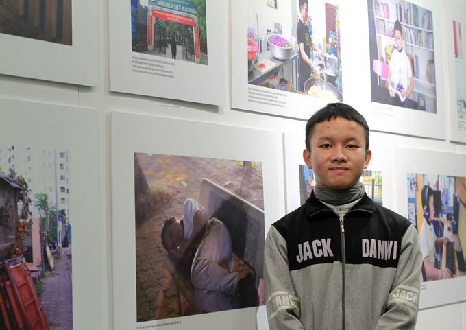 Giang A Trinh stands next to photos taken by him and of him during the 24 Hours On The Sheet exhibition at the Vietnamese Womens Museum in Hanoi. Photo by VnExpress/Phan Duong.