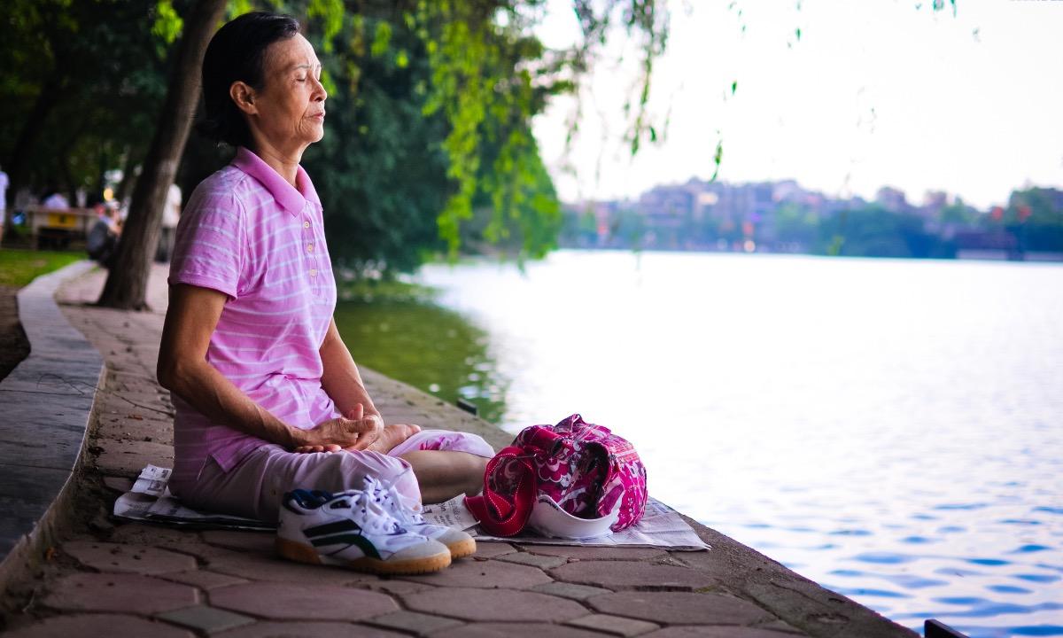 A woman meditates by Hanois Hoan Kiem Lake. Photo by VnExpress.