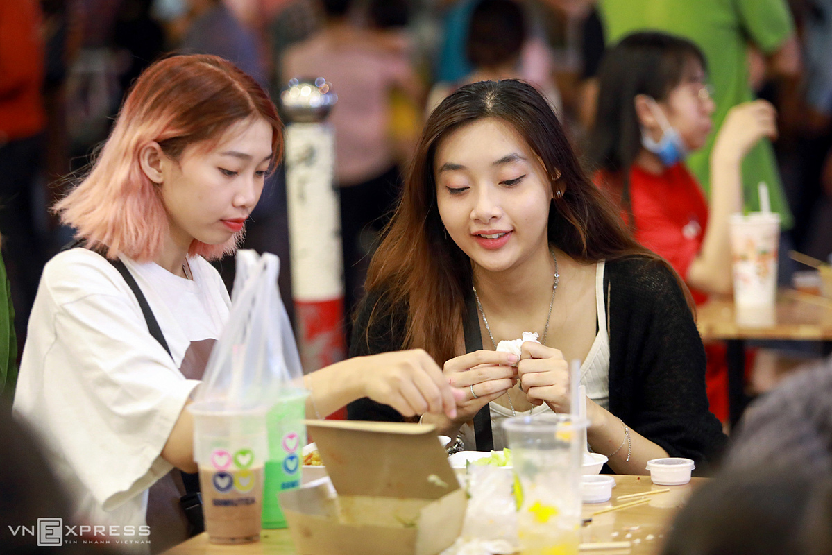 Ngo Diem Vy, (R) enjoys night food with her friend. This pedestrian zone is smaller than the one on Nguyen Hue Boulevard but food stalls there are very diverse and there are no street vendors harrasing customers, Vy said.