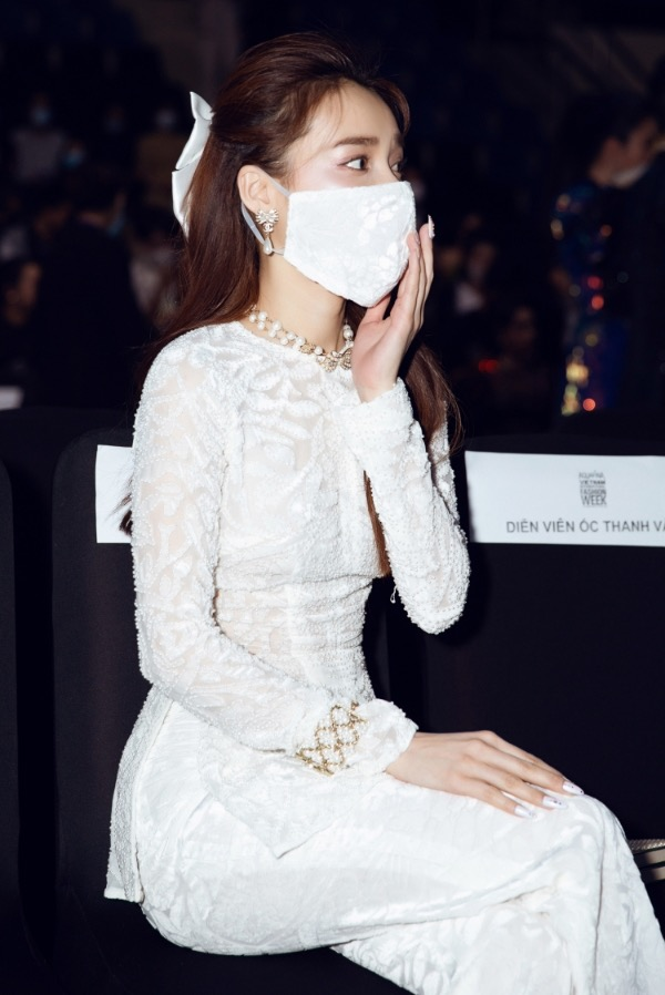Wearing a white outfits to attend another fashion show, Phuong chooses a mask having the same color.