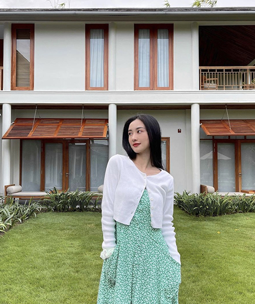 Model and actress Jun Vu in an outfit mixing a cropped cardigan with a floral dress while at a resort.