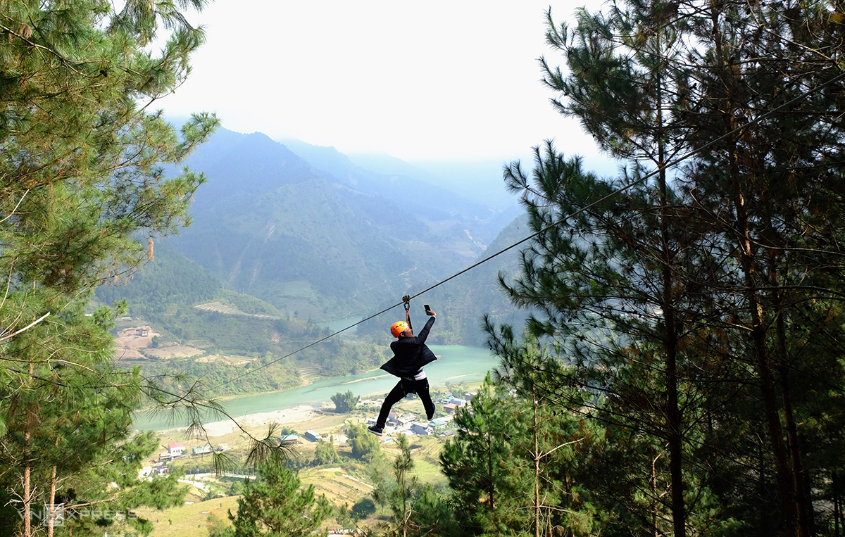A younger traveler captures his zip-lining experience on the phone. Photo by VnExpress/Khanh Tran.
