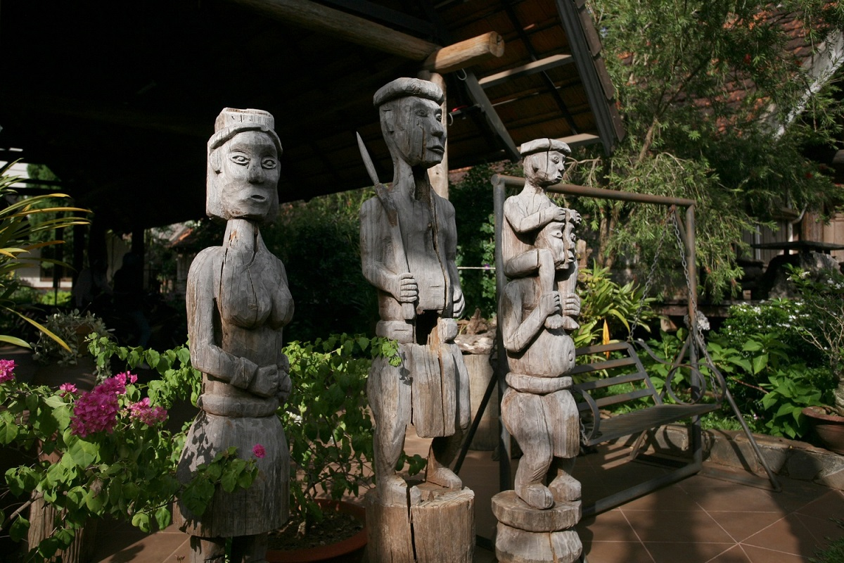 In the yard are wooden folk statues and furniture with intricate ethnic carvings.
