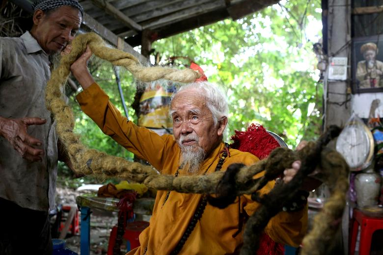 Nguyen Van Chien, 92, shows off his five-meter-long hair at his home in southern Tien Giang Province. Photo by Reuters/Yen Duong.