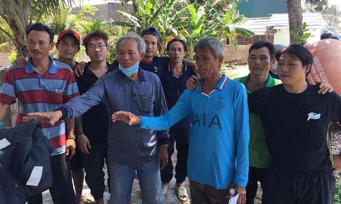 Anding Nadie Repil (blue T-shirt) poses for a photo with Vietnamese fishermen who rescued him while catching seafood on April 17, 2020. Photo by Pham Kha.
