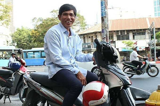 Tran Van Binh sits on a new motorbike he bought from donation of traffic police officers in HCMCs District 1, February 2020. Photo by VnExpress/Diep Phan.