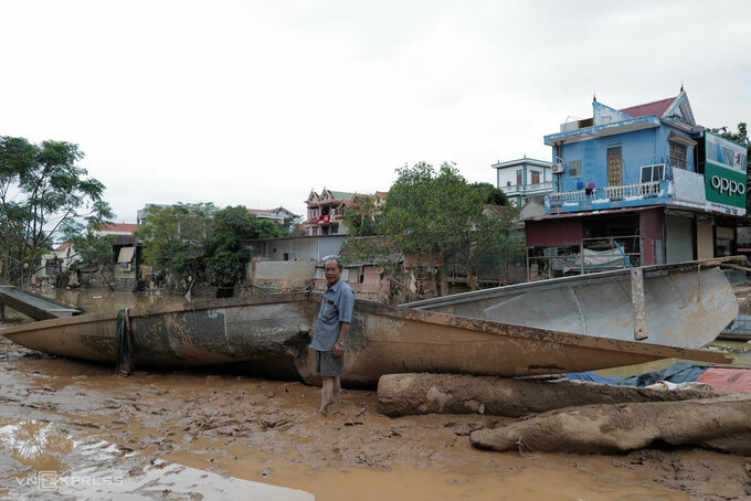 Vo Van Binh stands by his damaged boat after the floodwaters recede in Quang Binh Province, central Vietnam hit by multiple storms and floods, October 2020. Photo by VnExpress/Ngoc Thanh.