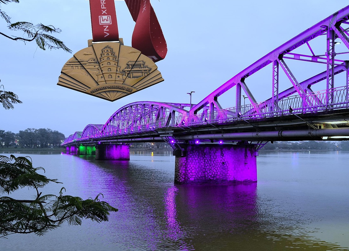 VM Hue medal with red colored lanyard by the Trang Tien  Bridge spanning the Huong River. Photo by VnExpress/Ngoc Thanh.
