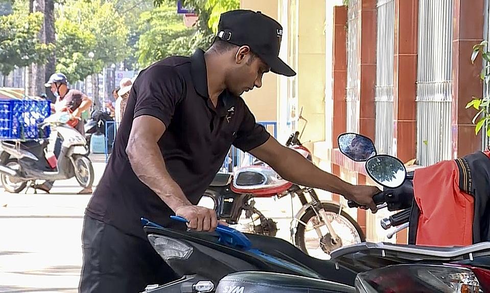 Arun Kumar walks a motorbike at the corner of Tran Hung Dao and Tran Dinh Xu streets. Photo by VnExpress/Hoang Huy.