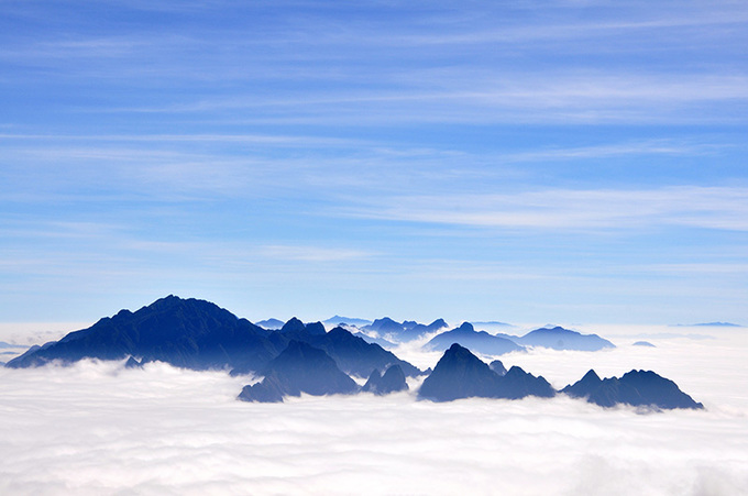 The mountain tops look like islands floating in a sea of white clouds.