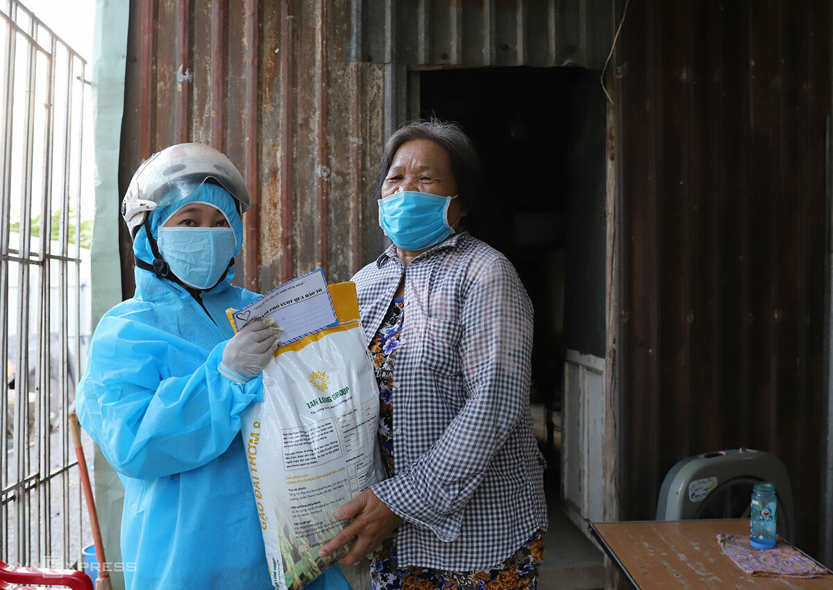 Covered in a protective suit, a volunteer of Nams group hands over a bag of rice to a woman at her house in Da Nang City, August 2020. Photo by VnExpress/Nguyen Dong