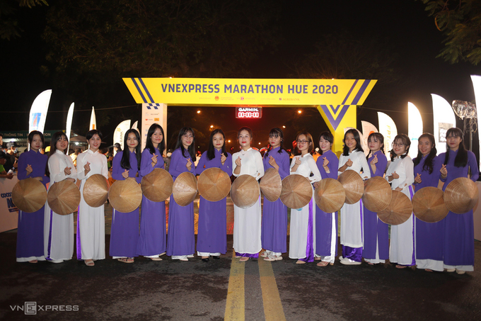 Women wearing the iconic ao dai of Hue cheered thousands of runners at the starting line.