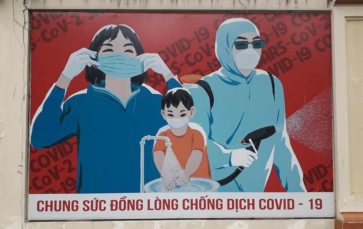 A poster on a street wall in HCMC calls people to stay united in fighting Covid-19. Photo by Samantha Coomber.