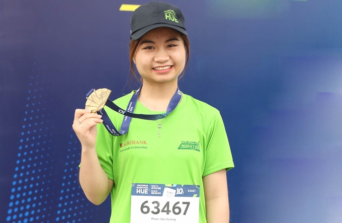 Pham Thien Ha holds her medal after finishing the 10 km distance at VnExpress Marathon Hue on December 27, 2020. Photo by VnExpress/Pham Chieu.
