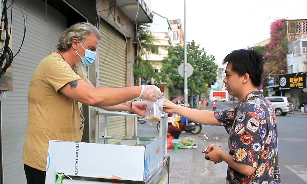 From prepping and selling fried cakes off a small sidewalk cart, Fabrice has received a lot of attention from both locals and tourists alike.