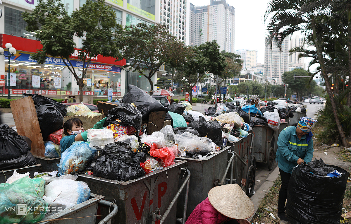 Dozens of trash-filled carts inundate on Ham Nghi Street and occupy halfway, making it difficult for people to travel during rush hours.