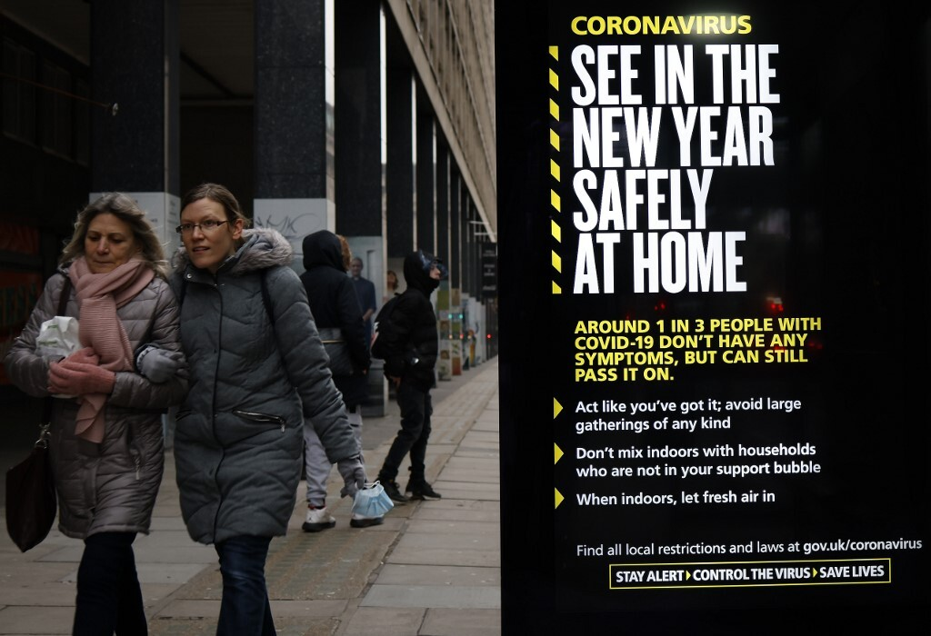 Pedestrians walk past a bus stop in London with a government message about the coronavirus urging people to take precautions on December 29, 2020. Photo by AFP/Tolga Akmen.