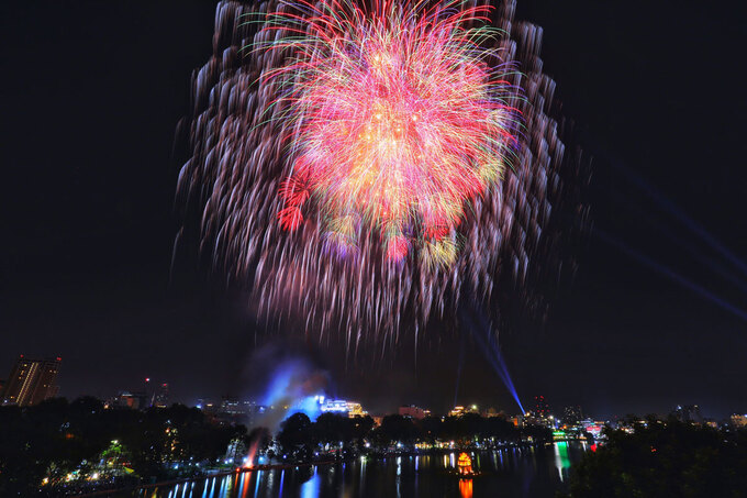 Fireworks seen over the Hoan Kiem Lake in Hanoi. This is the first time the capital city set off fireworks for New Year since 2016, when the government asked localities to spend that money helping the poor. Photo by VnExpress/Ngoc Thanh.