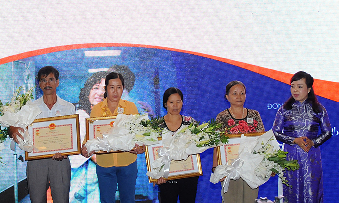 Former Minister of Health Nguyen Thi Kim Tuyen (R) with families of organ donors including a mother (second from left) who had donated her sons organ at a ceremony in 2016. Photo courtesy of Du Thi Ngoc Thu.