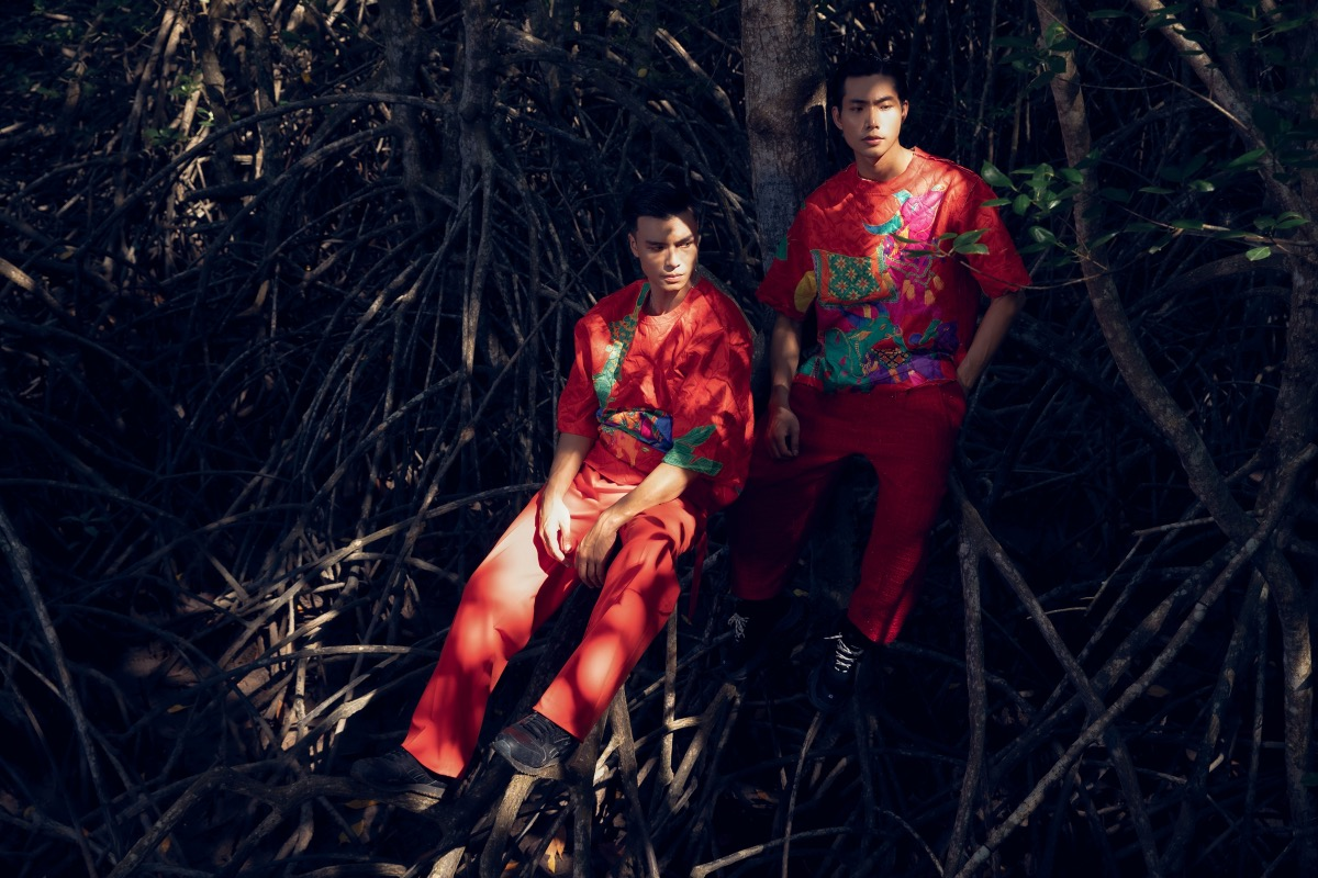 Male models wear red brocade shirts with traditional patterns.