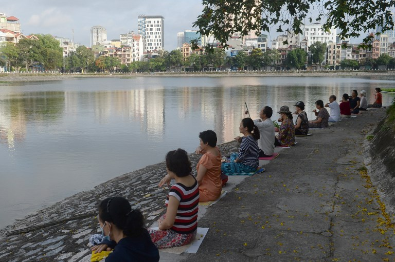 People practice meditation next to a lake in downtown Hanoi, June 10, 2017. Photo by AFP/Hoang Dinh Nam.