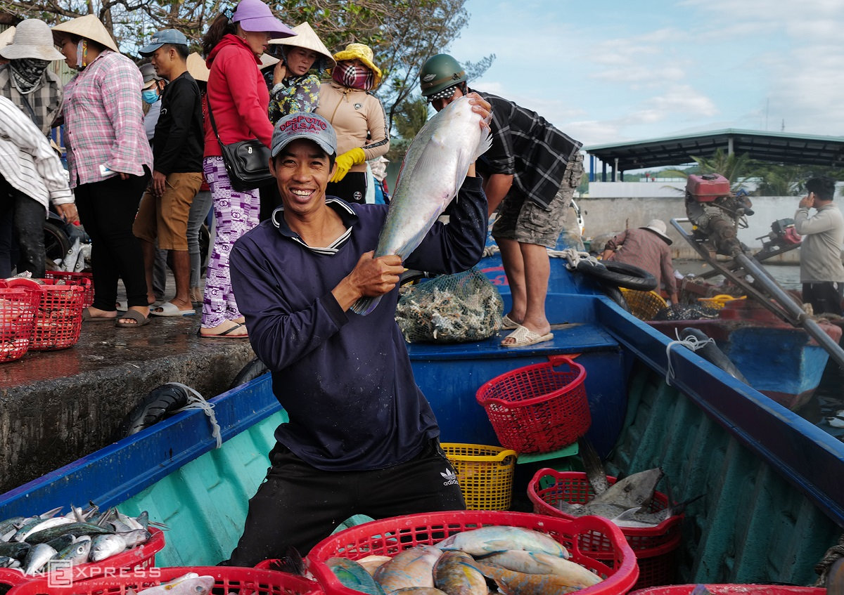 Returning from a long journey out at sea, Huynh Van Minh shows off his huge catch with a wide smile.  Smaller boats are tasked with transferring fish to land for wholesalers from the larger fishing vessels.  Minh used to work as a taxi driver but has turned to fishing because of travel restrictions imposed by the Covid-19 pandemic, and to avoid the monthly service fee of VND700,000 ($30.34) he had to pay the taxi company. Now, he usually earns around VND500,000 ($21.67) a day fishing.