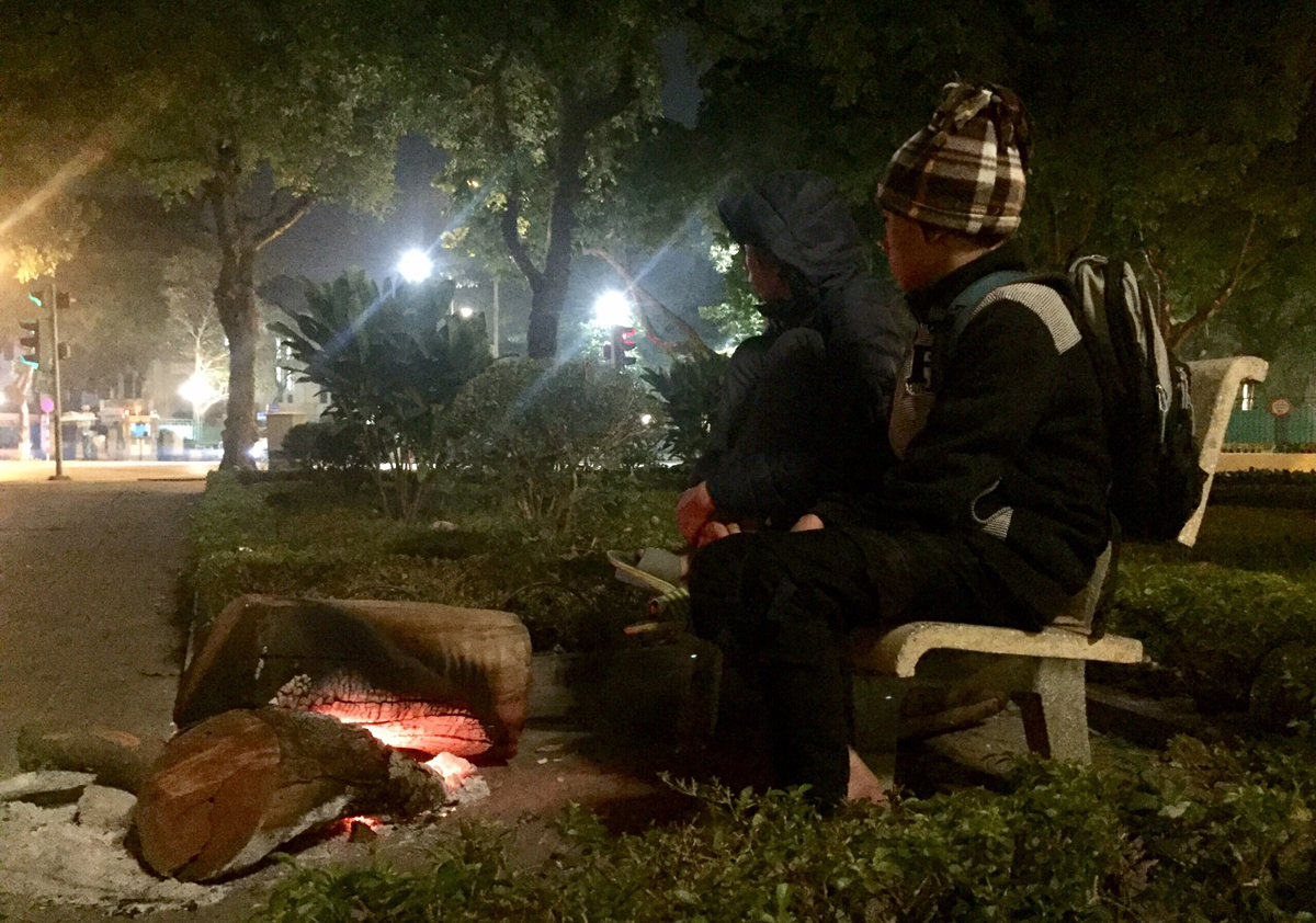 Two homeless boys sitting by a fire in a park in Tay Ho District, Hanoi, on January 21, 2021. Photo courtesy of Hoang Anh.