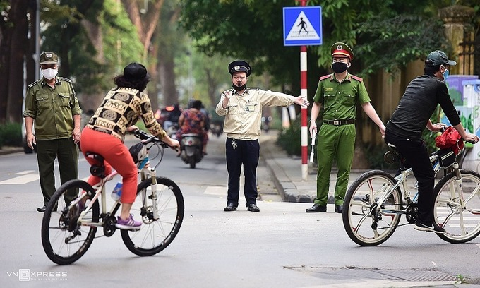 Two people riding bicycles in Hanoi are reminded by police officers not to exercise on the streets to comply with the nationwide social distancing campaign, April 9, 2020. Photo by VnExpress/Giang Huy.