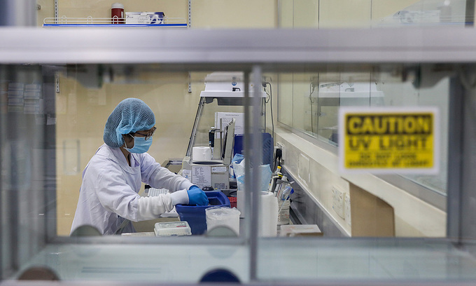 A medical worker tests novel coronavirus samples in a lab in HCMC, April 2020. Photo by VnExpress/Quynh Tran.