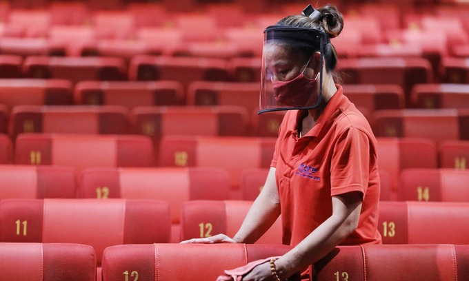 An employee cleans seats at Galaxy Cinema in Saigons District 1, May 9, 2020. Photo by VnExpress/Quynh Tran.