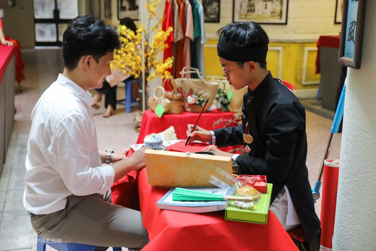 A calligrapher  (in black dress) writes beautiful characters which are expected to herald good lucks for the New Year. The event also featured a reenactment of fortune telling that used to be popular during Tet by reading straws or quoting the renowned poem 'The Tale of Kieu' by the great poet Nguyen Du of the 19th century.