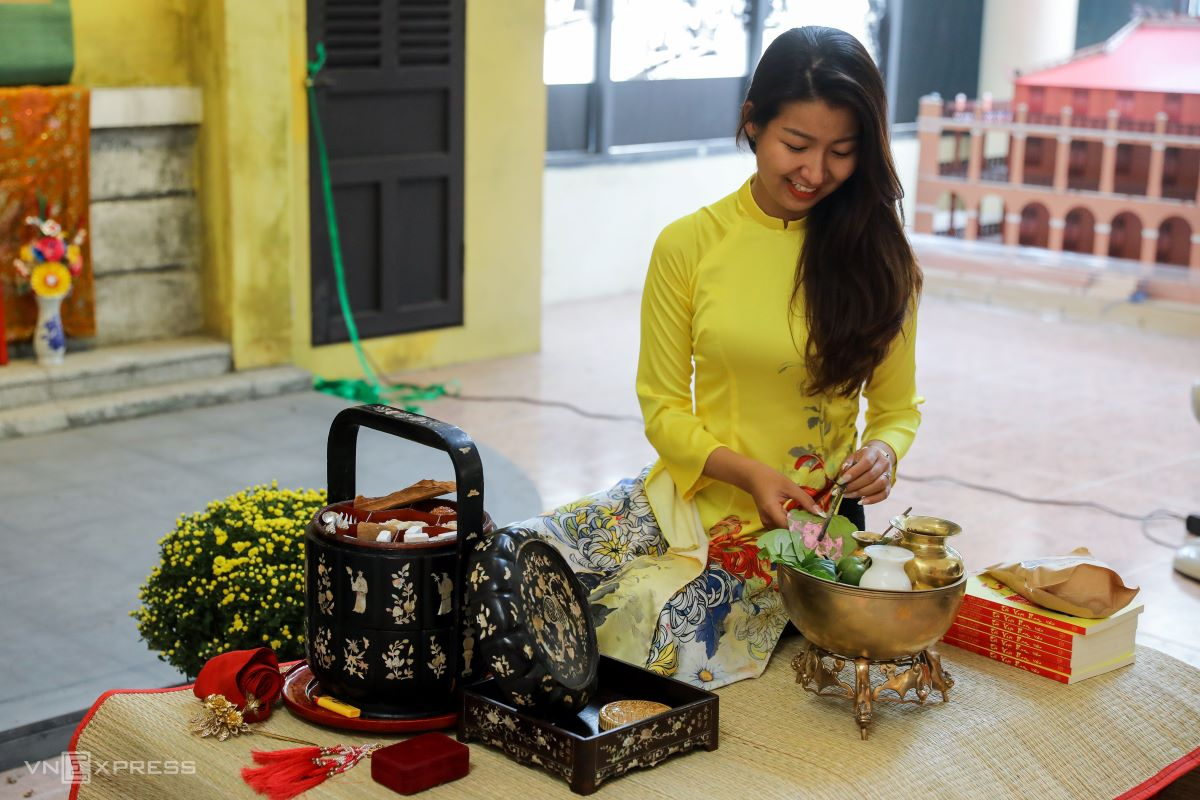 The house owner welcomes guests to a space near the altar. Yellow flowers such as daisy and apricot are displayed in the living room. Guests are offered sweets, tea and 'trau cau' (betel leaf and areca nut).