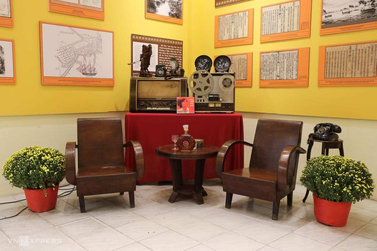 A living room with furniture from the 1960s and an old tape recorder and radio on the mantelpiece.