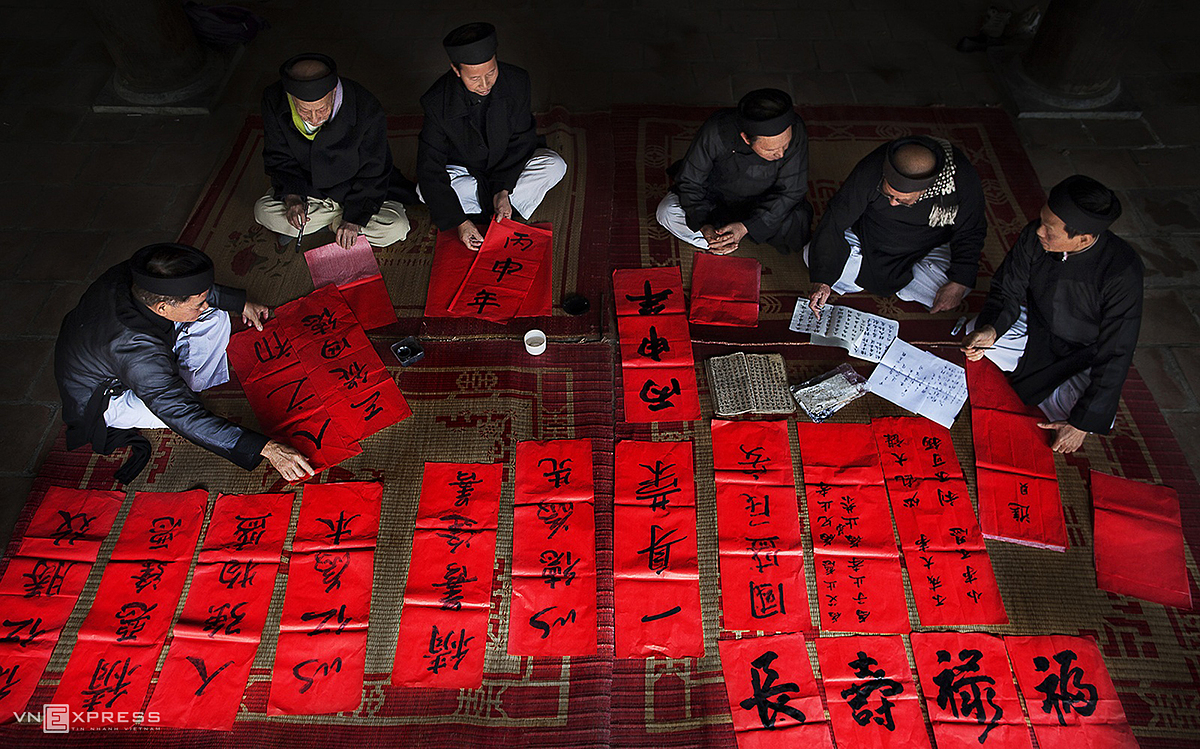 Calligraphers write calligraphy couplets on red paper in Tho Ha Village of Viet Yen District in Bac Giang province.Calligraphers are dressed similar to ong do, an archaic term for those who passed academic exams under Vietnam's old imperial regime. These scholars were usually teachers and adept in Chinese.