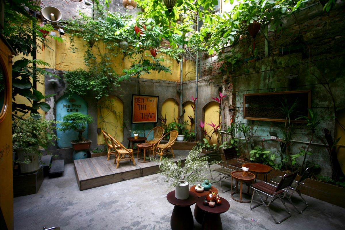 The backyard is decorated with green plants and boasts a small stage for live performances, all protected by a retractable canvas roof.