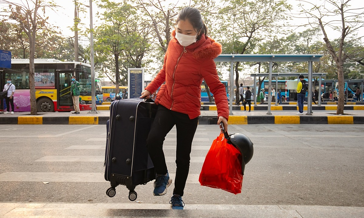 A student of Hanoi's University of Finance - Business Administration lifts her suitcase at the Giap Bat Station as she heads home for Tet, January 30, 2021. Photo by VnExpress/Tung Dinh.