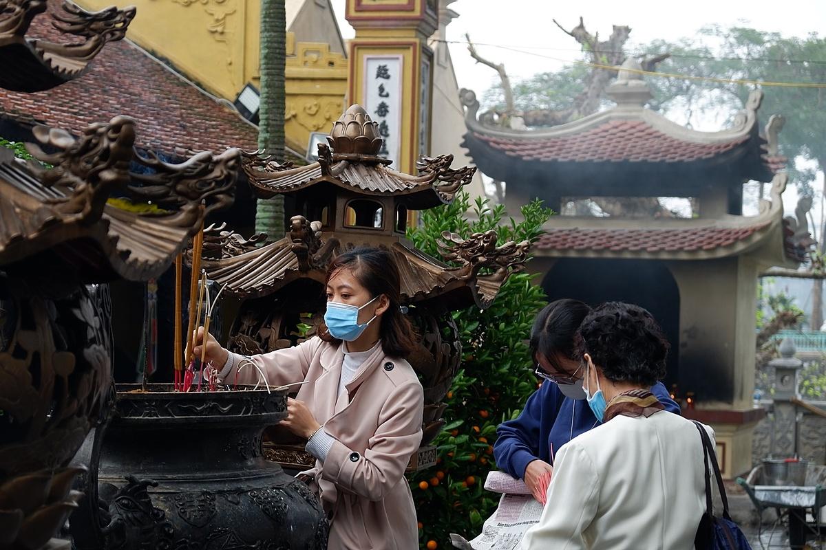 Some devout residents in face masks burn incenses inside Tran Quoc Pagoda.