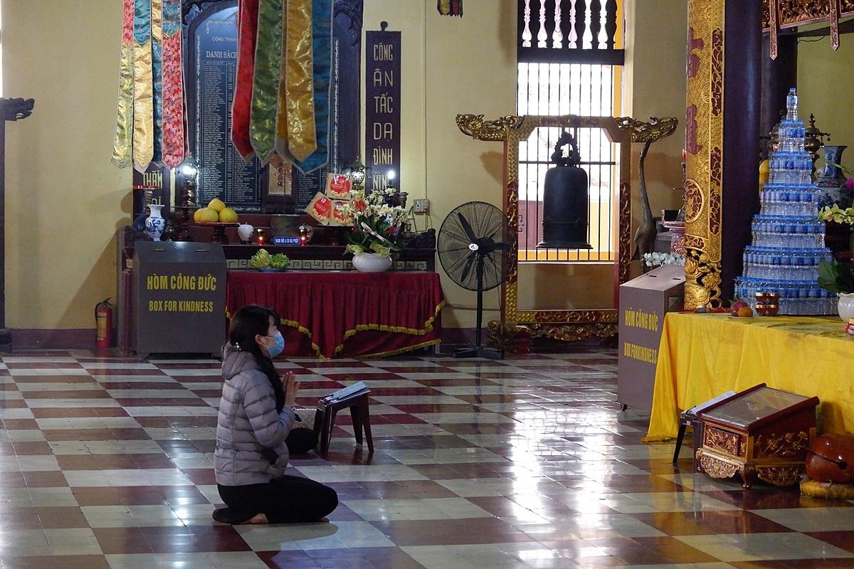 A woman wearning face masks prays inside Quan Su Pagoda in Hoan Kiem District.
