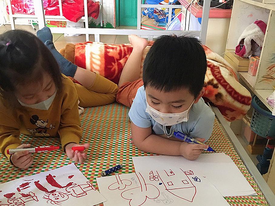 Khanhs son (R) draws with his friend.