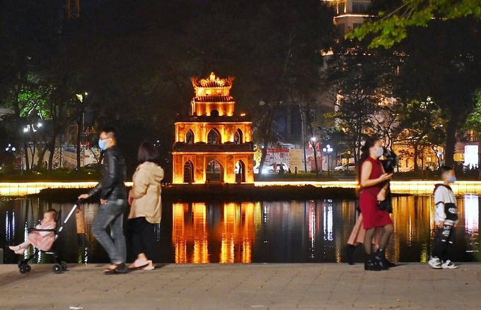 The usual crowd was missing in downtown Hanoi, but many intrepid residents gathered on the banks of the Hoan Kien Lake to walk around the decorated area and enjoy the Lunar New Year's Eve. Photo by Giang Huy.
