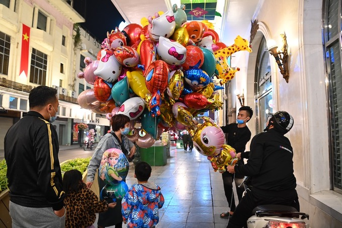 A family took their kids to Trang Tien Street and bought them balloons.