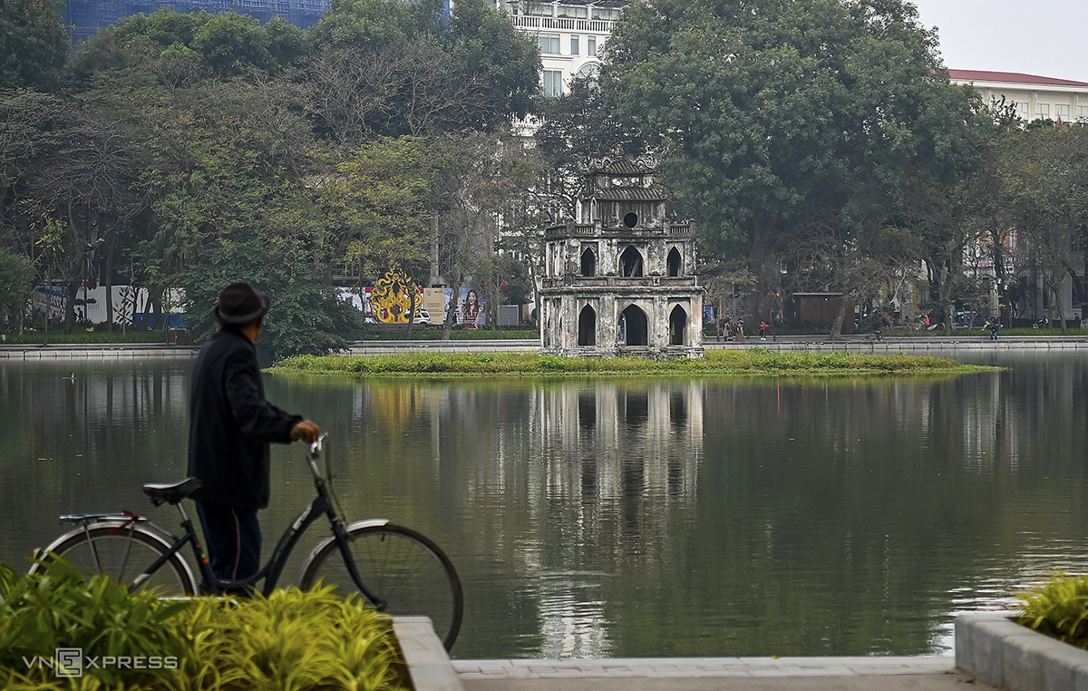 A senior citizen walks his bicycle by the iconic Hoan Kiem Lake in the heart of Hanoi early Friday morning.