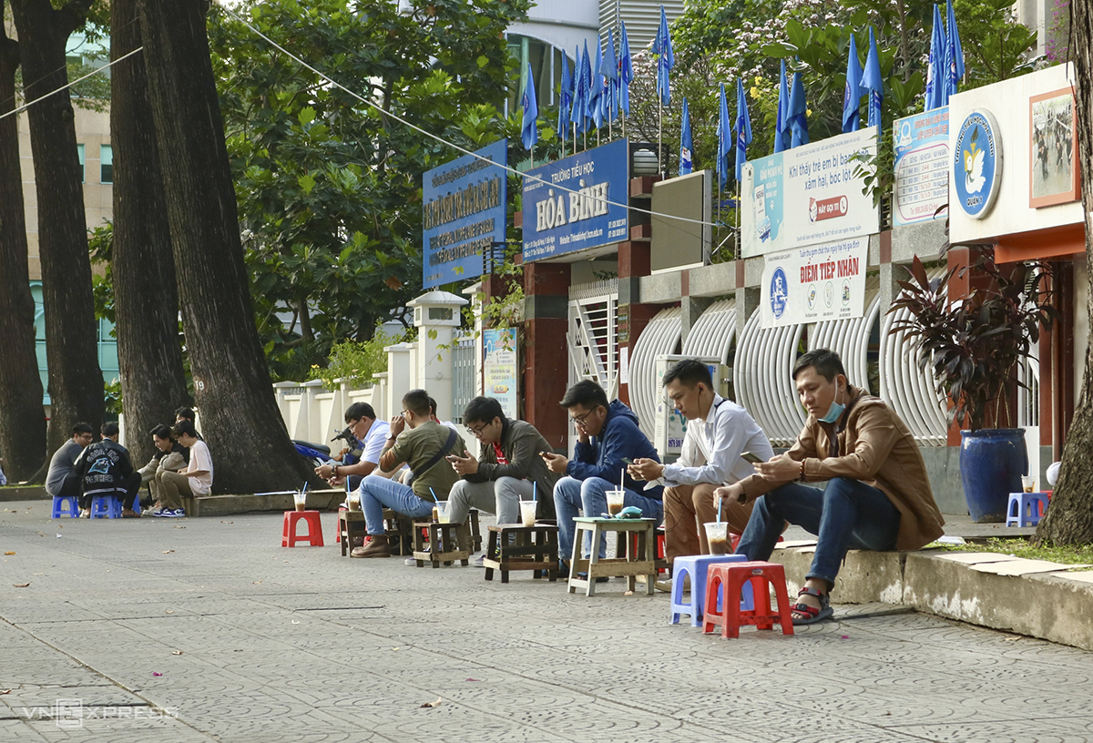 A handful of people are glued to their cell phones as they enjoy iced coffee in the sidewalk across the Notre Dame Cathedral in HCMC.The HCMC administration last week shut down bars, karaoke parlors, cinemas and discotheques, and banned religious events following a new Covid-19 outbreak.