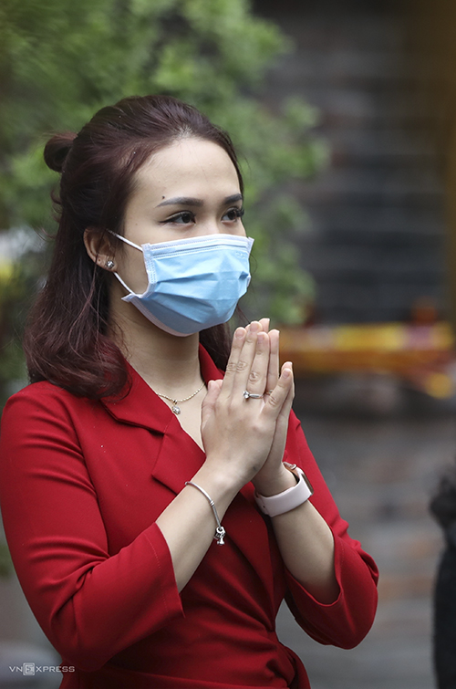A woman keeps her face mask on while praying.