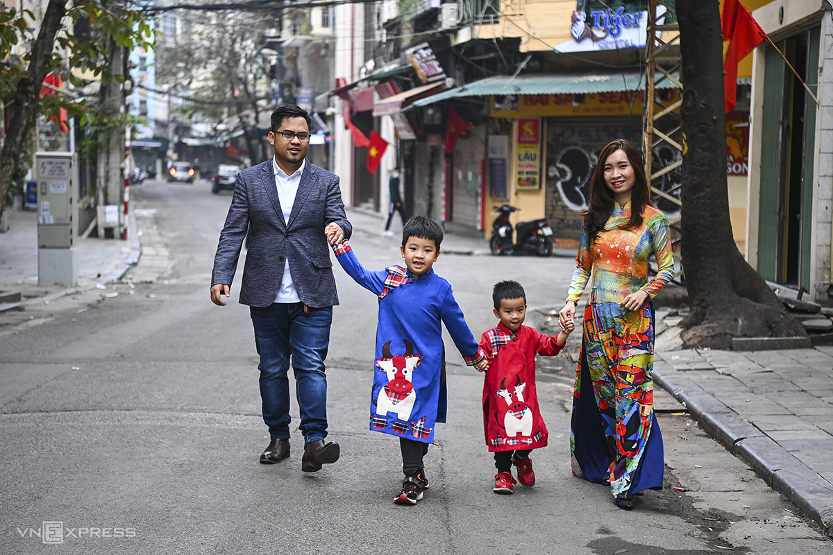 A local family on their way to relatives' homes, the mother and two boys wearing ao dai, the traditional Vietnamese tunic.