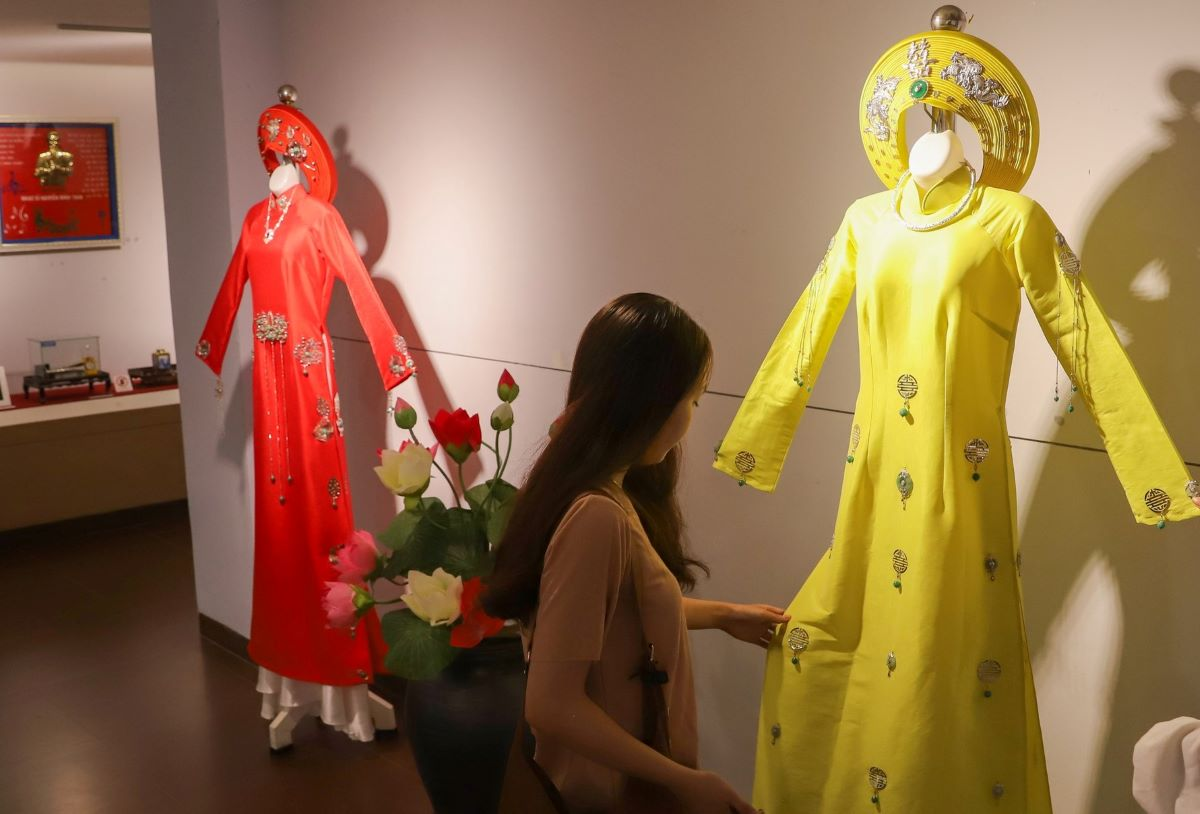 Two young women admire an ao dai with Mong's silver decoration.