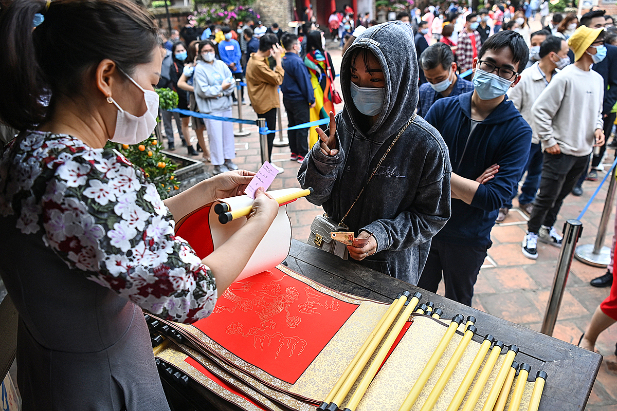 People line up to get blessings in calligraphy on red or yellow do paper priced at VND100,000 ($4.35) per sheet.
