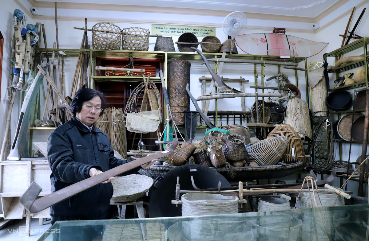 More than 200 agricultural tools are kept by Cuong.  In the photo, he holds a stick that was used to carry feasts and offerings in the past.