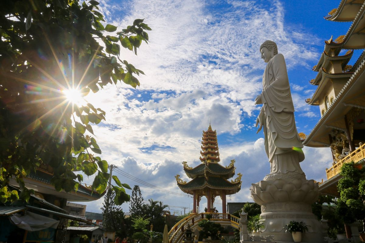 The 15-meter marble Buddha statue at the entrance facing a small lotus temple to the Bodhisattva basks under the Saigon sunshine.