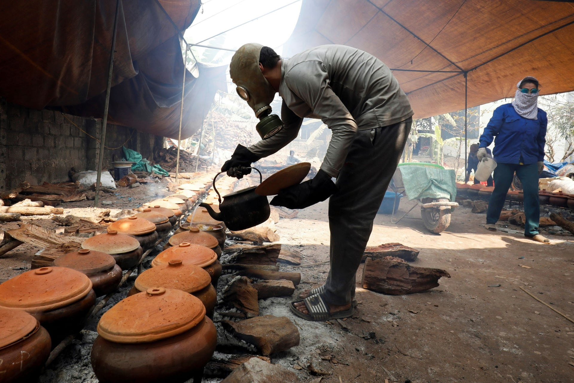 Bui Van Cuong wears a gas mask as he braises black carp in clay pots with firewood to serve as a traditional Vietnamese dish, Ha Nam Province. Photo by Reuters/Kham.